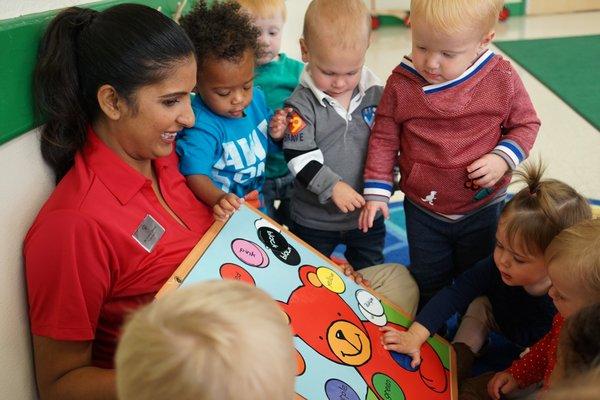 children gathered around teacher